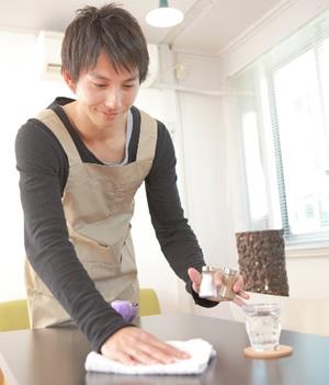 カフェのテーブルを片付ける男性
