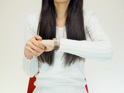 腕時計をみる女性